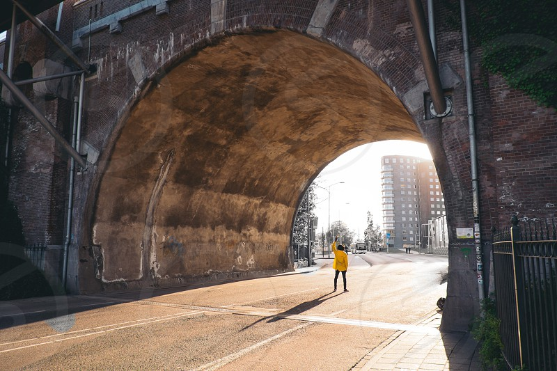 person in yellow jacket standing under gray concrete archway at daytime photo