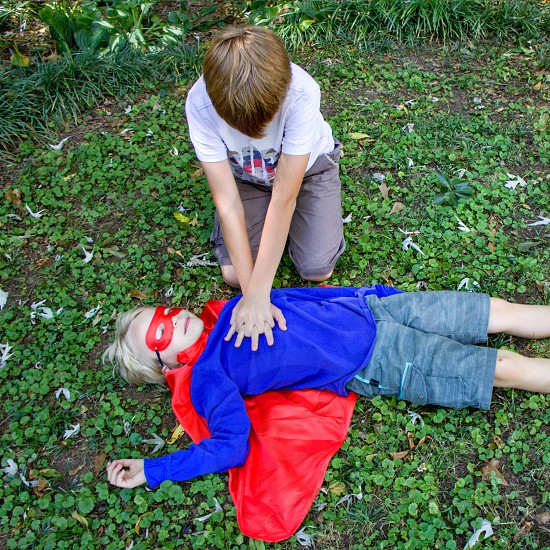a boy in white t shirt trying to resuscitate another boy wearing a blue long sleeve and red cape as he lay on a grassy area during daytime photo