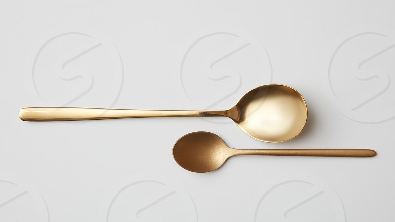 Tea and dessert golden spoons isolated on a gray background. Time to eat concept flat lay photo