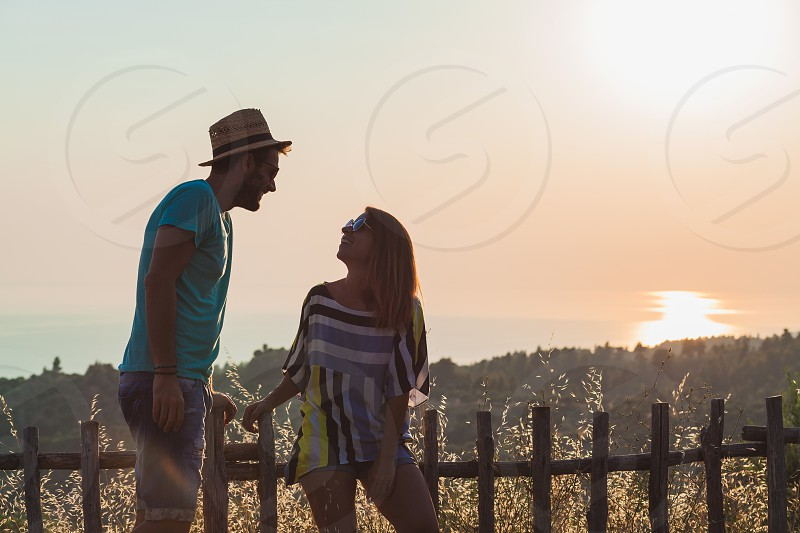 Young couple in love enjoying sunset over the sea photo
