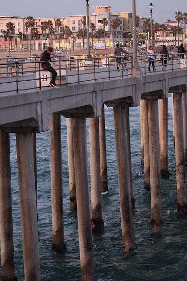 man in black jacket sitting on handrail suspension bridge during daytime photo