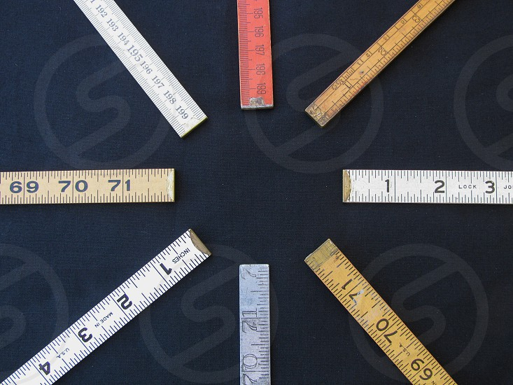 A circle arrangement of folding rulers on black limbo suggests concepts of measurement precision accuracy with center copy space. photo