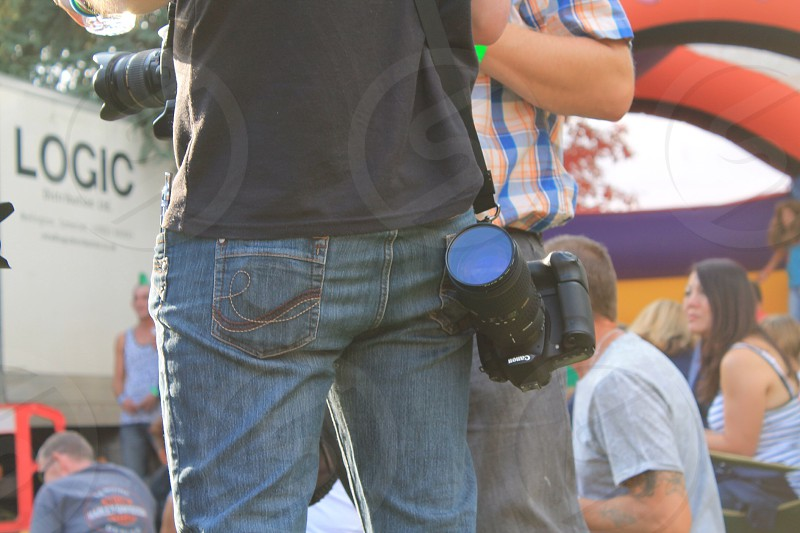 All good photographers keep their lens caps in their back pockets ! Shooting at an open air festival. Canon.  photo