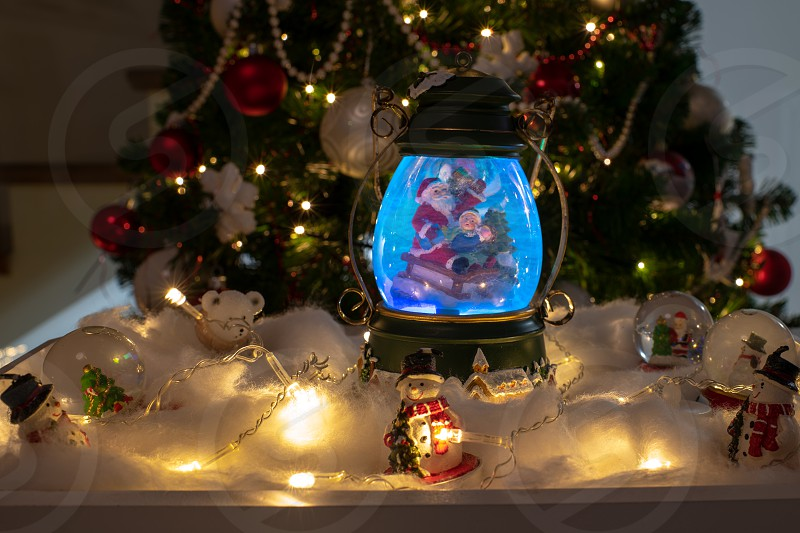 Christmas decoration snow dome globe with table decoration Santaclaus on sleigh with child in winter scene with snowflakes reindeer snowglobe and polar bears tree in background photo
