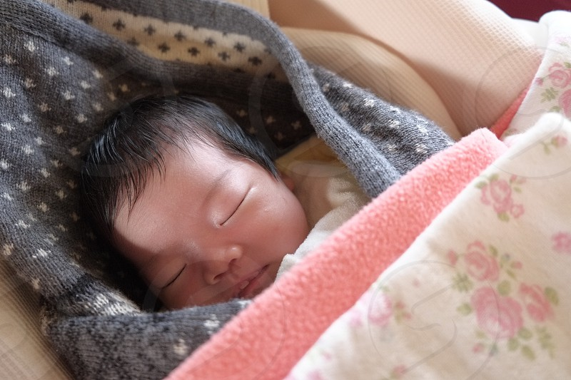 infant with black pink and white floral blanket photo