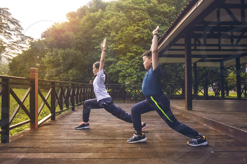 Athletic young brother and sister do exercises practicing yoga in nature outdoor park during sunrise morning moment wearing sports outfit. concept of Healthy lifestyle training workout photo
