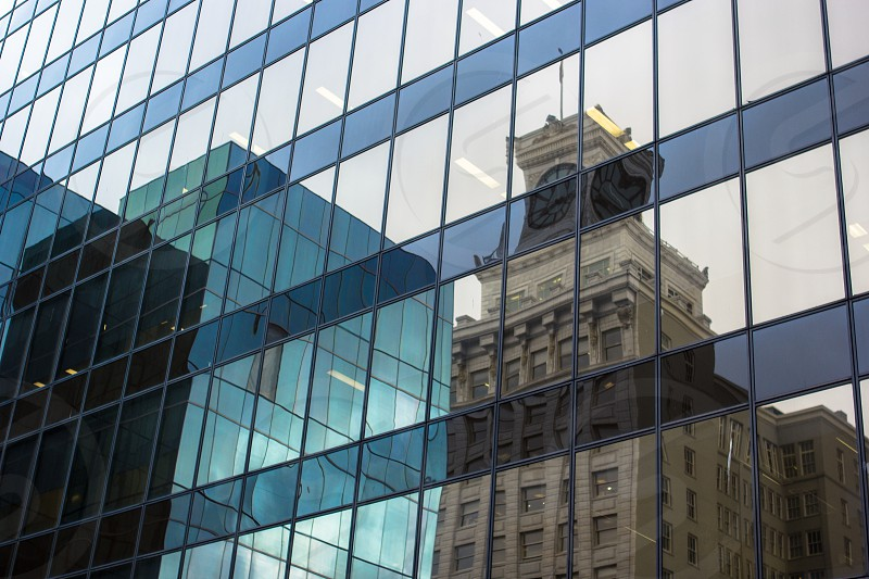 a Clock tower building reflecting in another building photo
