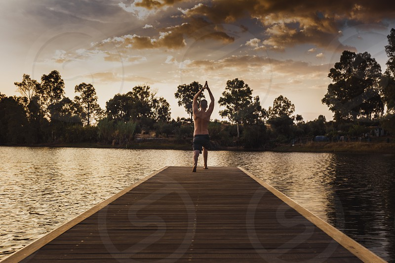 Young man without shirt on his back doing yoga on the edge of the wooden jetty at sunset photo