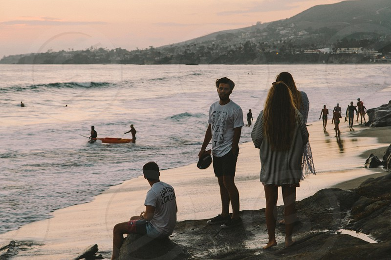 A group of friends watching sunset at the beach photo