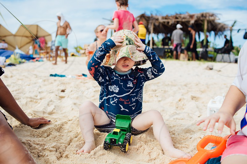 family travel sport activity young kids adult swimming beach ocean playing  summer sit play hat enjoy outside day toddler kid hawaian hawai clothes toys photo