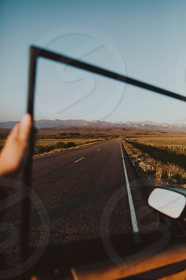 hand holding door open with window rolled down showing endless open road with mountain range in background photo
