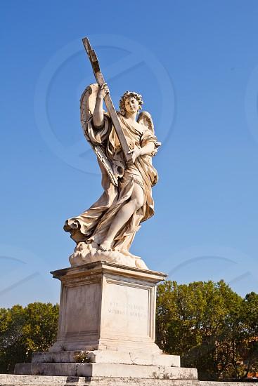 angel holding cross concrete sculpture photo