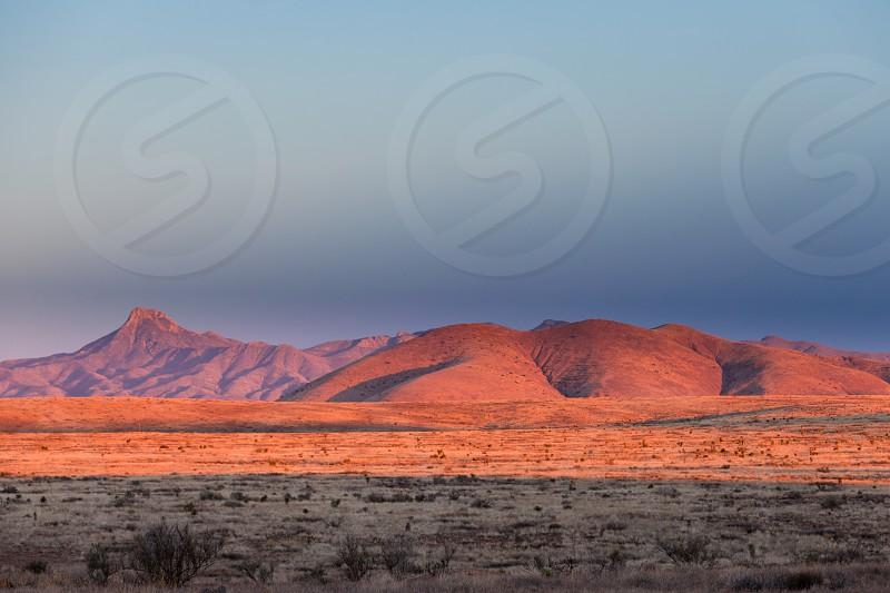 Sunset light on arid hills in barren high desert landscape of southern New Mexico NM USA photo