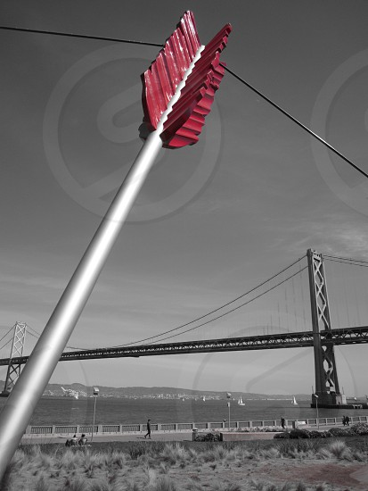 selective color photography of red arrowhead near Oakland Bay Bridge photo