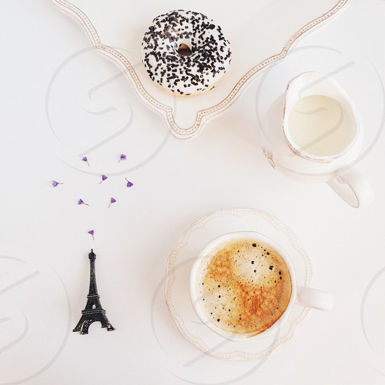 eiffel tower beside cup with cappuccino photo