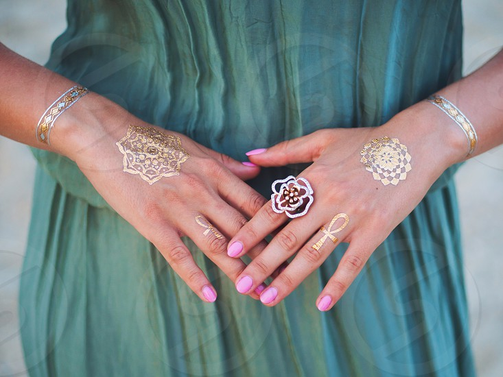 Silver and golden flash tattoo on female hands over sea or ocean background photo