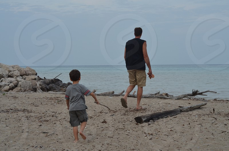 Father and Son Walking on the Beach  Water Lake photo