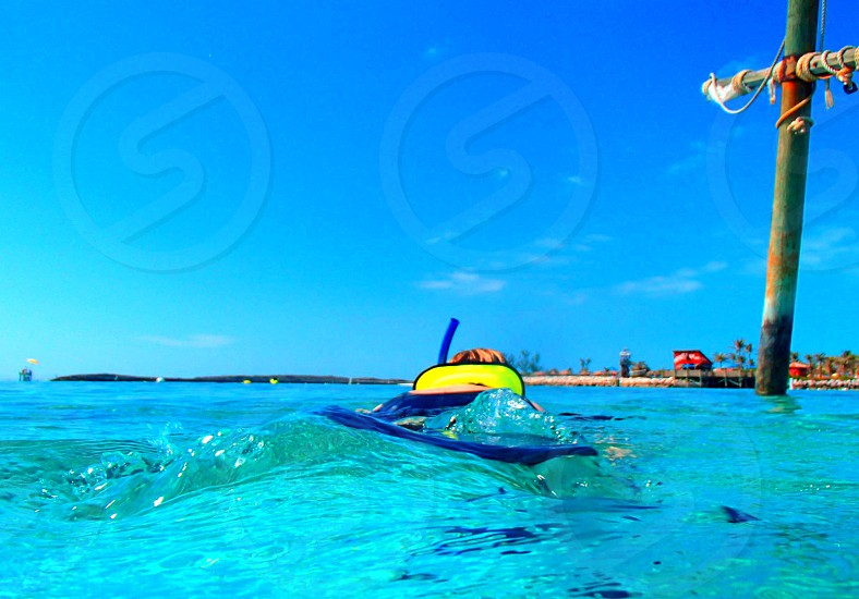 person snorkeling in clear blue water near post photo
