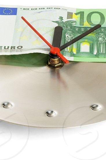 euro bill on a metal wall clock on white background photo