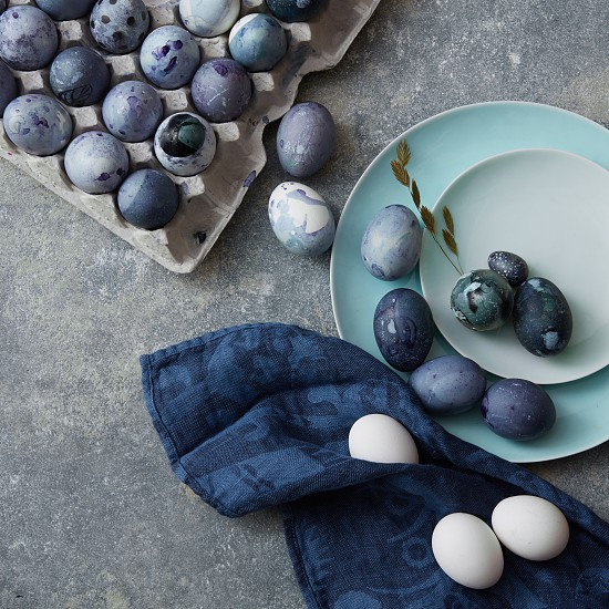 Blue Easter eggs with fluttering on blue plates and in a paper box with a blue napkin on a concrete gray background is shot from above photo