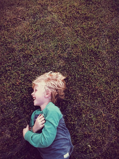 A little boy laughing on the grass. photo