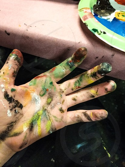 left human hand with multicolored  paint photo
