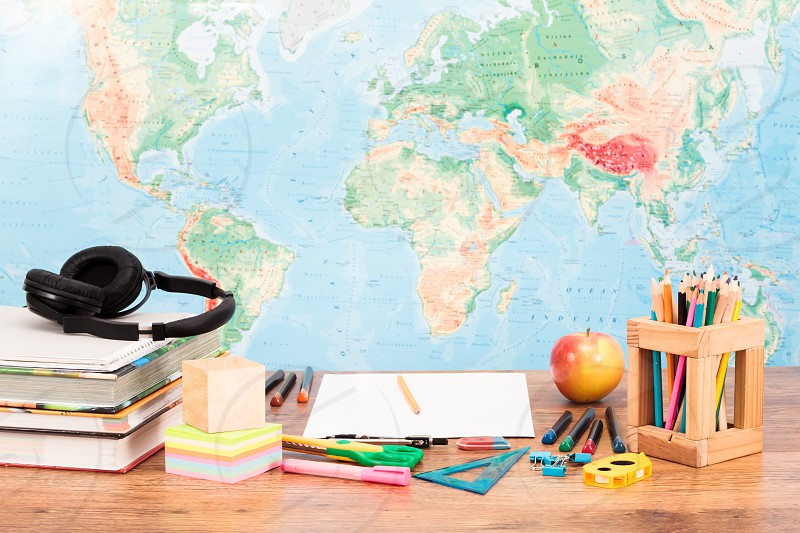 School accessories on desktop with map at background photo