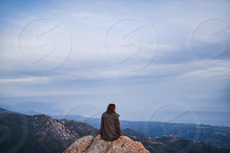 girl woman outdoors mountains reflect sky clouds view rock hike ponder photo