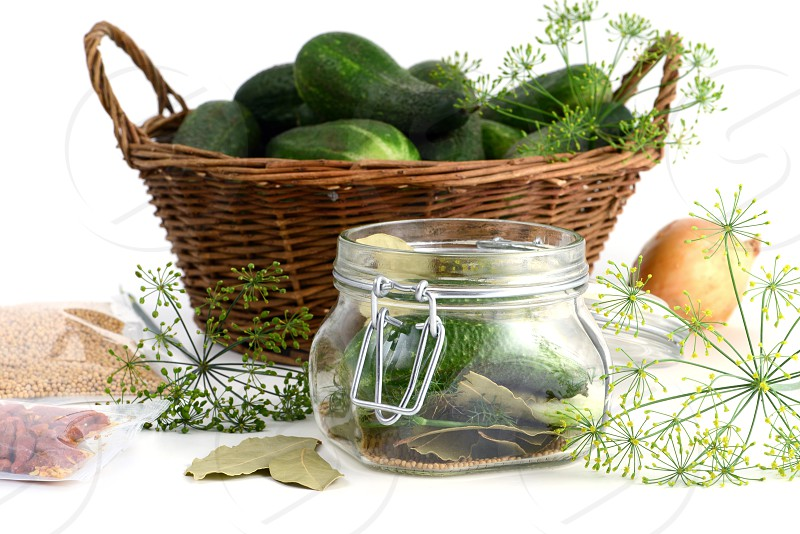 homemade cucumbers in jar glass with herbs like dill laurel leaves chili peper and onions. photo