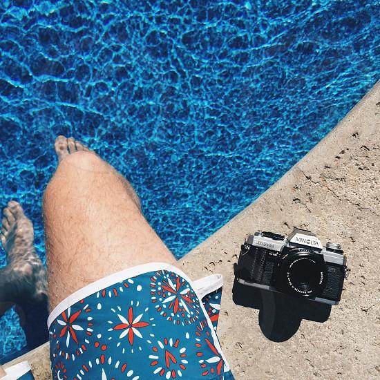man wearing blue red and white floral shorts beside black minolta mirrorless camera beside inground swimming pool photo