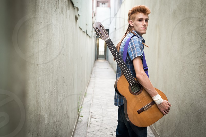 young adult men musician in long corridor with folk guitar photo