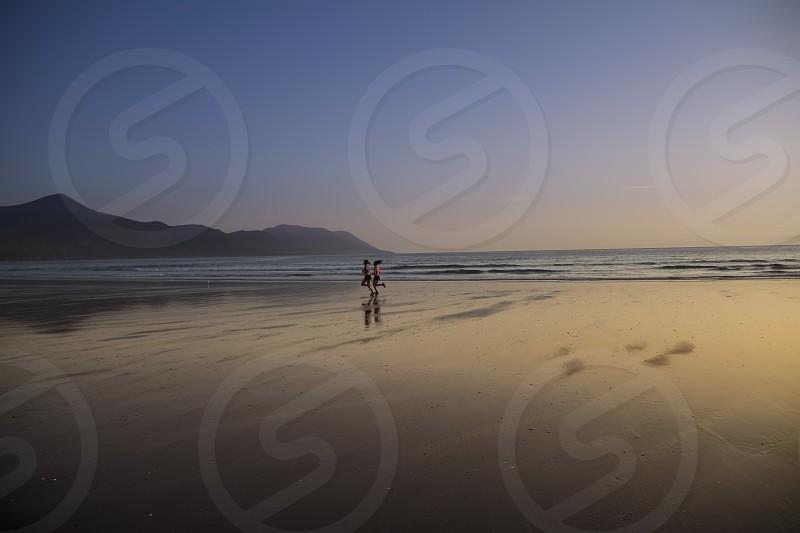 2 women running on shore photo