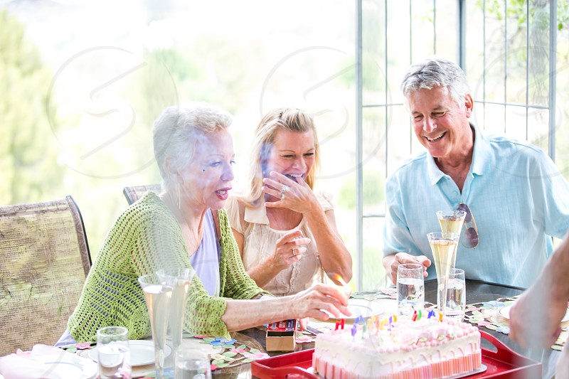 Baby Boomer Birthday Friends celebrating cake and champagne photo