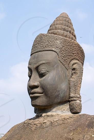 CambodiaAngkor Wat- March 2018: The head of one of the Stone Asuras holding the nāga Vasuki on a bridge leading into the 12th century city of Angkor Thom.  photo