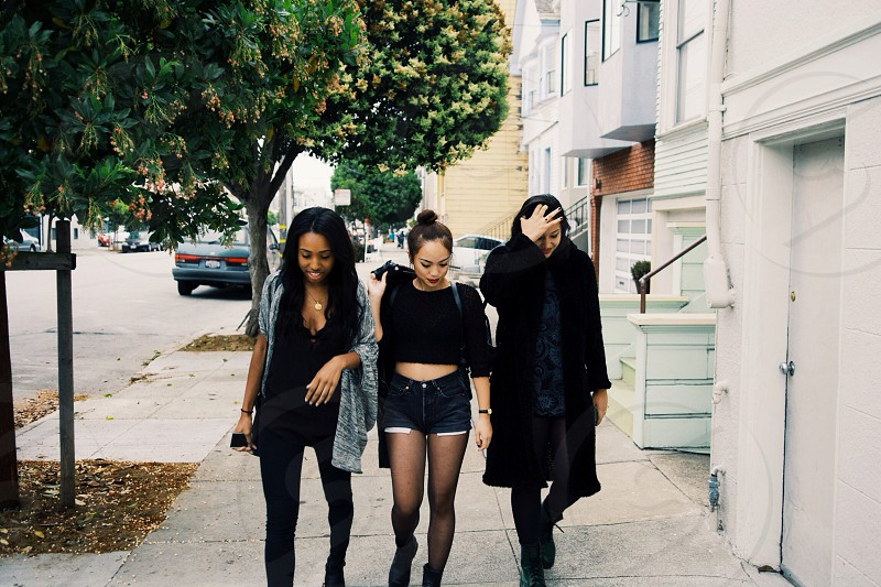3 women on walkway beside apartment buildings photo