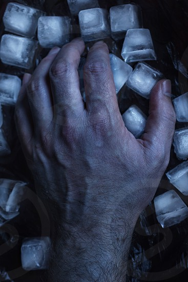 close up photography of person holding ice cubes on black surface photo