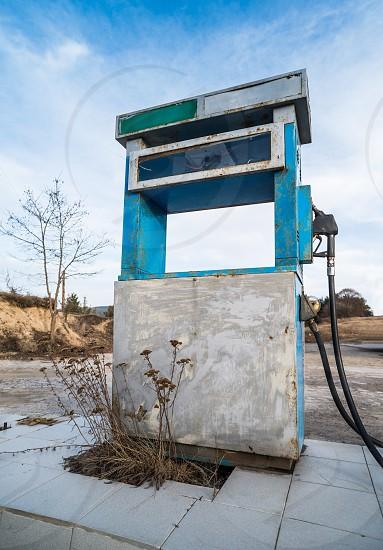 Vintage old gas pump on blue sky photo