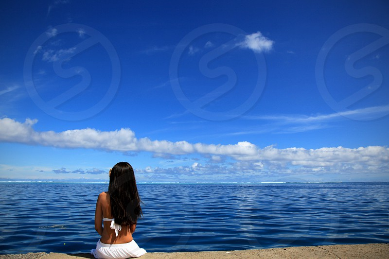 woman sitting in front of ocean view photo