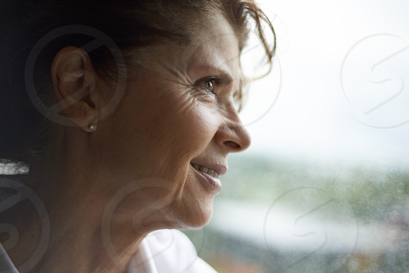 Elderly woman looking out of a rainy window looking for someone with a hopeful expression photo
