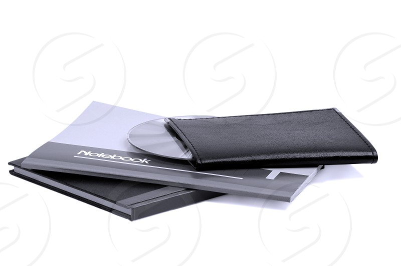 assorted notebooks with a cd flat piled on white backgroundblue filter photo