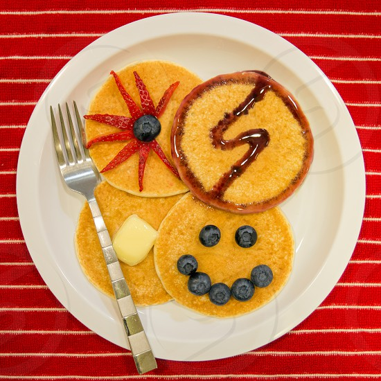On a plate of pancakes adorned with fruit and butter the Snapwire logo appears in a trail of blueberry syrup. photo