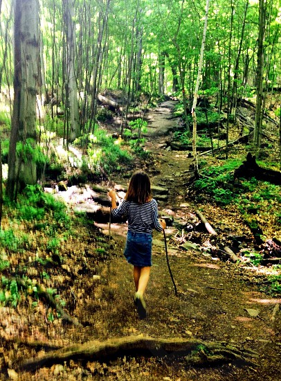 girl walking in the woods with a stick photo