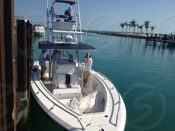 white boat on blue water with 3 person photo