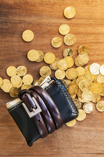 Wallet tied with belt and gold coins spread over wooden tabletop photo