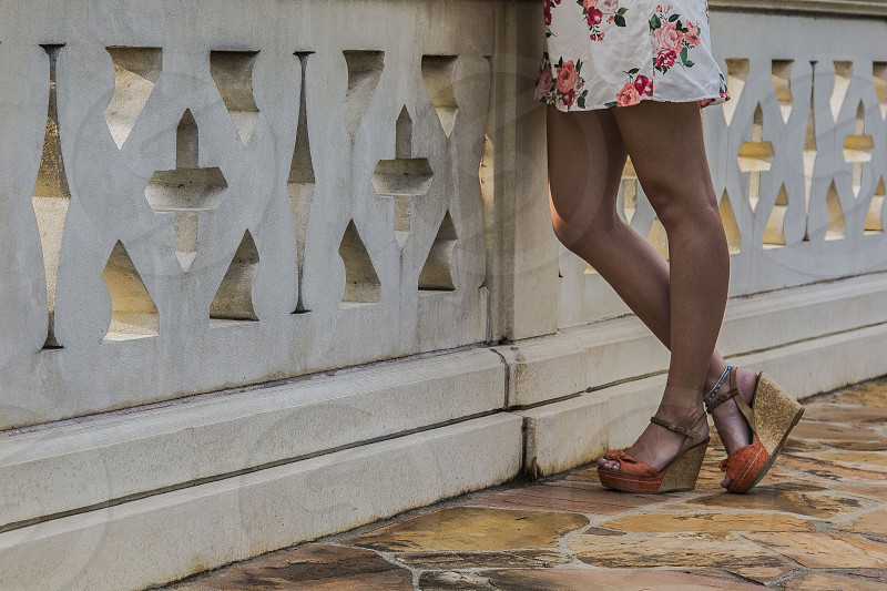 woman wearing white and pink floral mini dress and pair of brown cork sandals photo