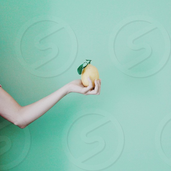 hand holding yellow pear against green wall photo