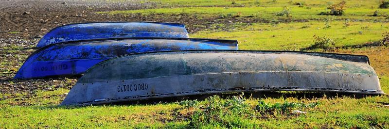 three upside down boats on grass photo