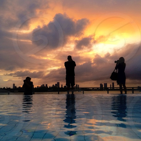 3 persons taking picture in swimming pool  silhouette  photo