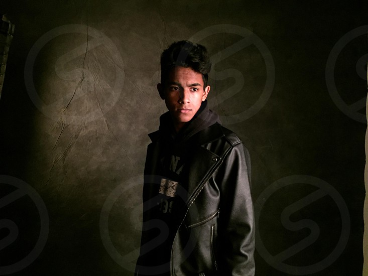 Man poses in dramatic light wearing a leather jacket over a hoodie. photo
