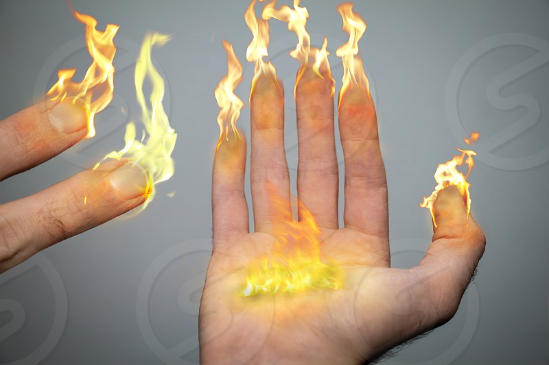 Right hand and fingers are on fire like candles or torches. Being an inspiration of the Hanukiah (menorah). 8 fingers symbolizing the menorah candles and a big flame in the middle of the palm symbolizes the Hshamash.Seven lit candles. photo